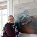 Kunstneren Anne-Cathrine Nannestad Pettersen står fremfor et maleri med tekstur som hun selv har malt.