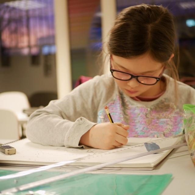 Fotografi av en jente som sitter og tegner.