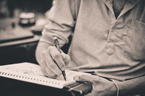 Fotografi av en mann som sitter og tegner.