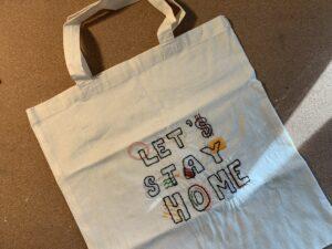 """Bilde av et handlenett som Oda Hope har brodert teksten """"Lets stay home"""" på."""